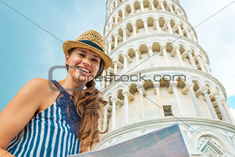 Portrait of happy young woman with map in front of leaning tower