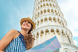 Happy young woman with map in front of leaning tower of pisa, tu