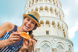 Portrait of happy young woman with pizza in front of leaning tow