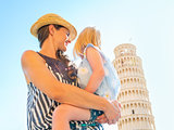 Mother and baby girl looking on leaning tower of pisa, tuscany,