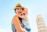Happy mother and baby girl hugging in front of leaning tower of