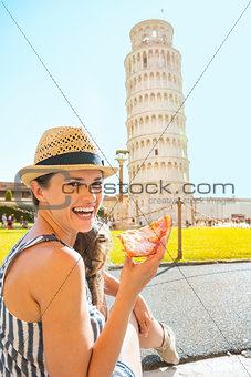 Portrait of happy young woman eating pizza in front of leaning t