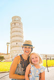 Portrait of happy mother and baby girl in front of leaning tower