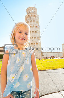 Portrait of baby girl in front of leaning tower of pisa, tuscany