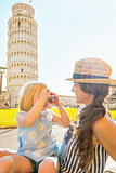 Baby girl taking photo of mother in front of leaning tower of pi