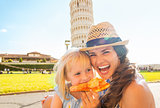 Portrait of happy mother and baby girl eating pizza in front of