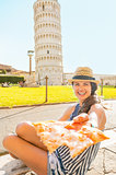Young woman giving pizza in front of leaning tower of pisa, tusc