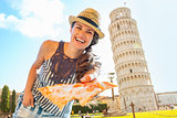 Smiling young woman giving pizza in front of leaning tower of pi