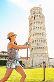 Funny young woman supporting leaning tower of pisa, tuscany, ita