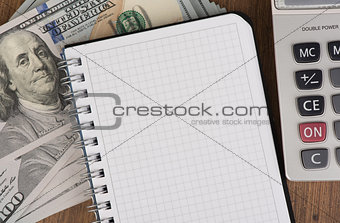 calculator and notepad lying on banknotes