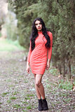 Hispanic young woman wearing orange dress in urban park