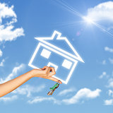 Hand holding house icon and key. Background of sky, clouds, sun