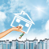 Hand holding house icon and key. Background of sky, clouds, sun, buildings