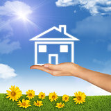 House icon on hand. Background of sky, clouds and sun