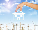 Hand holding house icon. Background of sky, clouds and sun, tower crane
