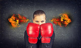 Woman boxing gloves covers her face. Fire from ears. Concrete gray wall as backdrop