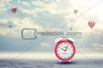 Alarm clock on concrete floor with background of clouds, hot air balloon