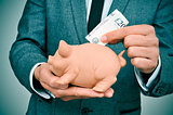 man in suit introducing a pound sterling bill in a piggy bank