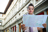 Young woman looking in map near uffizi gallery in florence, ital