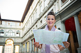 Portrait of happy young woman with map near uffizi gallery in fl