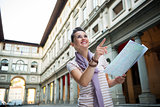Happy young woman with map pointing near uffizi gallery in flore