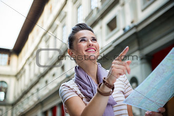 Portrait of happy young woman with map pointing near uffizi gall