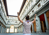 Young woman near uffizi gallery rejoicing in florence, italy. re