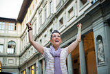 Happy young woman near uffizi gallery rejoicing in florence, ita