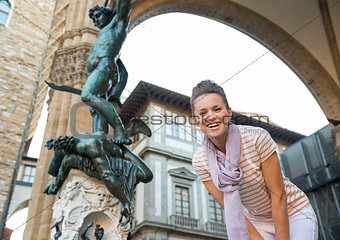 Portrait of happy young woman in front of statue perseus with th