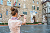 Young woman taking photo of palazzo vecchio in florence, italy.