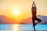 Pilates by the Sea. Girl balances at dawn