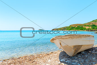 Old rowboat on shore blue sea
