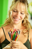 Young female artist looking at colored pencils and smiling
