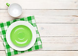 Empty plate, cup and towel over wooden table background