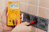 Electrician hands with multimeter measuring the voltage in a wal