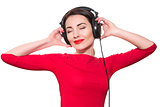 Attractive young adult woman in red clothes listening to the mus