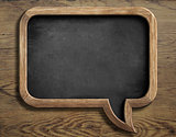 old chalkboard in shape of speech bubble on wooden background
