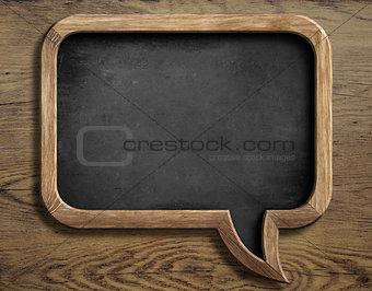 old chalkboard in shape of speech bubble on wooden background