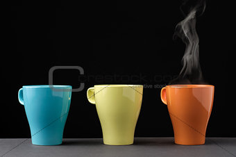 Three colorful mug with steam
