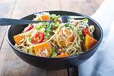 Bowl of pesto pasta with fresh vegetables