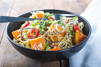 Bowl of pesto pasta with fresh vegetables
