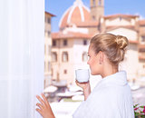 Drinking coffee near by window