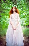Cute red-haired woman wearing white dress in a garden