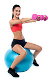 Woman in gym working out with dumbbells