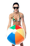 Bikini clad woman playing with beach ball
