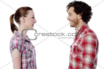 Casual young couple facing each other