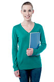 Charming student holding spiral notebook
