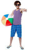 Cheerful guy with beach ball pointing at you