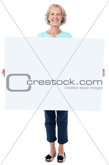 Casual old lady holding a blank billboard