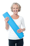 Gym instructor holding blue exercise mat